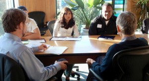 Advisors meet with students at a conference table